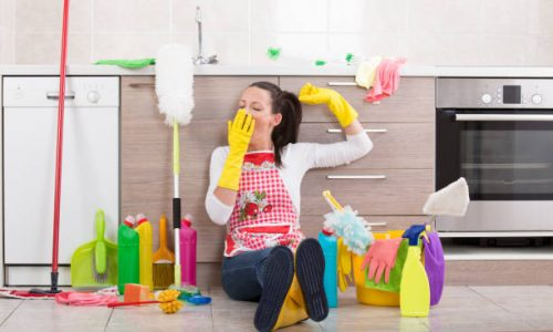 Tired young woman yawning and stretching on kitchen floor with bunch of cleaning products and equipment